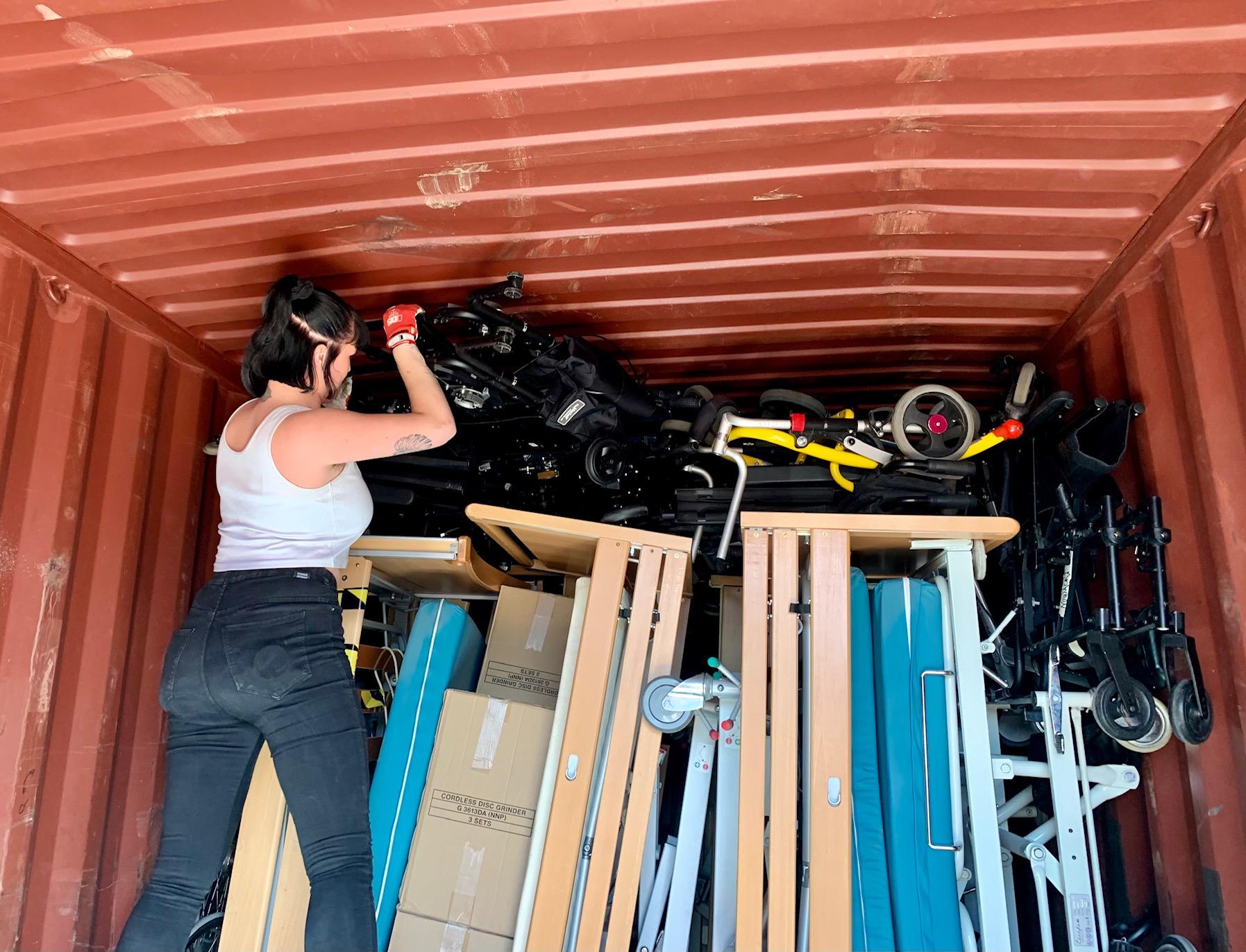 Kjerstin løfter på plass utstyr inne i en container